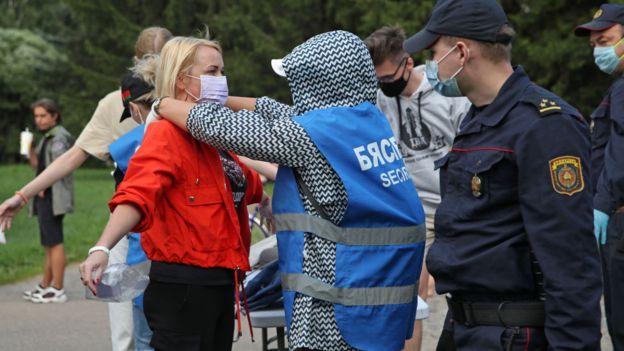 Женщину досматривают на митинге Светланы Тихановской