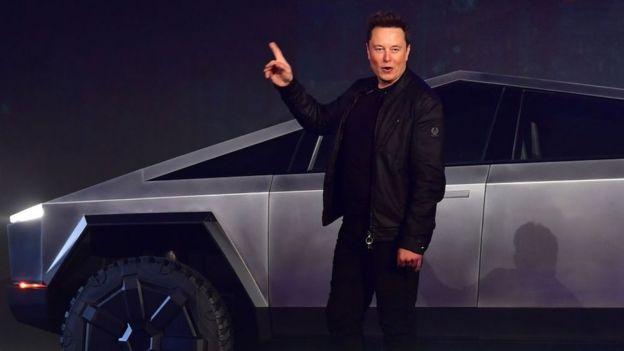 Elon Musk y uno de los autos de Tesla.