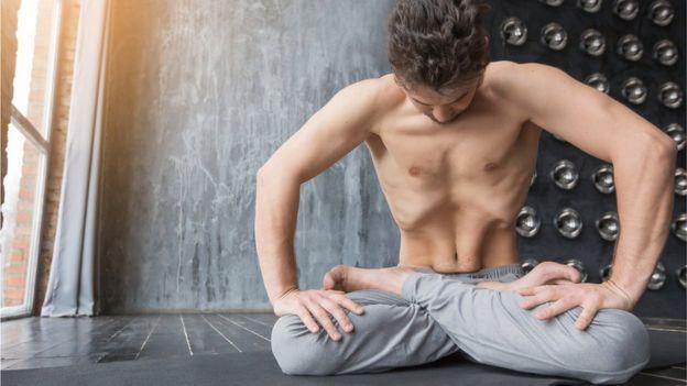 Hombre haciendo yoga mostrando su rectus abdominis