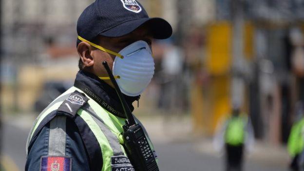 رجل شرطة يرتدي كمامة في الإكوادور