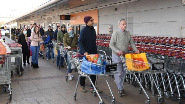 Alışverişçiler, 22 Mart 2020 güney Londra'da bir süpermarkette sıraya giriyorlar. Emekliler ve korunmasız insanlar, Coronavirus'un yayılması nedeniyle süpermarketlere akın eden ve Briton'un eşi görülmemiş taleplerinden dolayı temel alışverişlerini satın almak için mücadele ediyorlar.