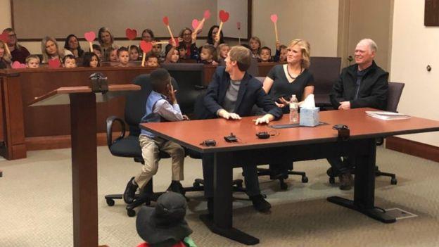 Niños agitan corazones de papel en un tribunal