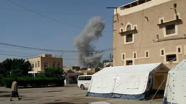 The aftermath of an air strike in the background of the al-Jumhori hospital, on the right
