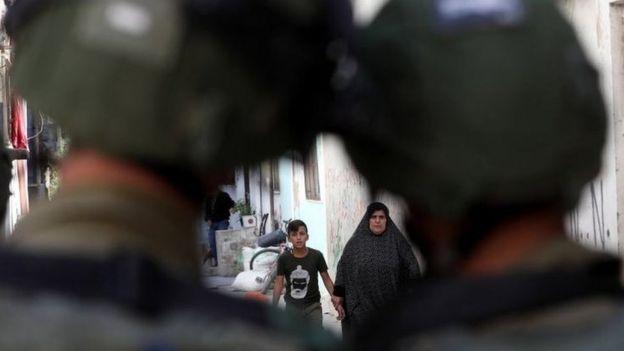 Palestinos andam em Hebrom observados por soldados israelenses