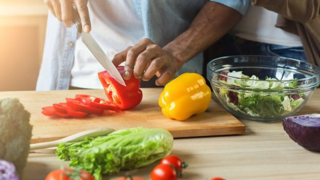 Man chopping a pepper surrounded by fresh produce