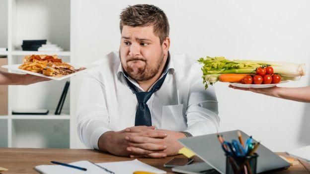 Hombre duda entre comida saludable y chatarra.