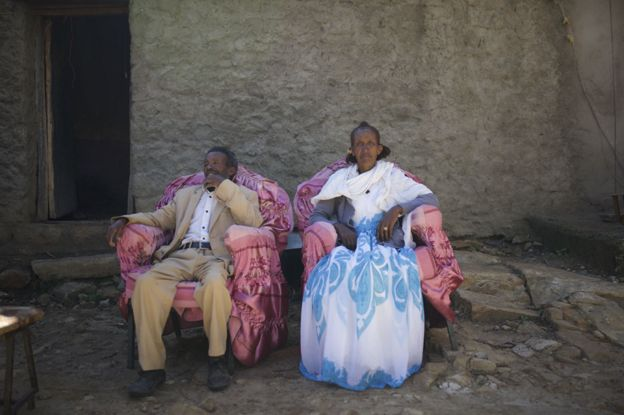 Two people sitting outside their home
