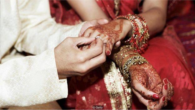 Marido coloca aliança no dedo da mulher