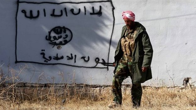 A Kurdish fighter walks by a wall bearing a drawing of the flag of the Islamic State (IS) group in the northern Iraqi town of Sinjar, in the Nineveh Province, on November 13, 2015.