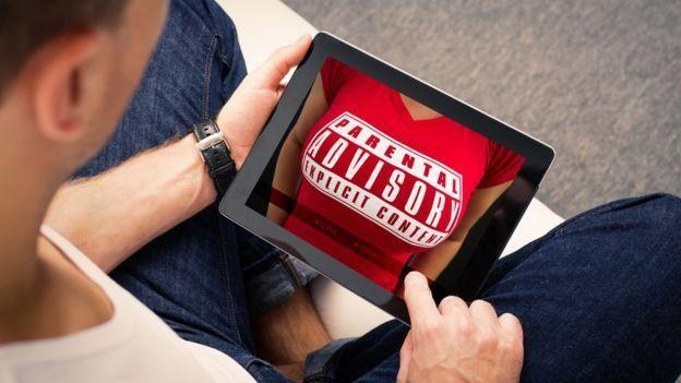 Hombre mirando pornografía en una tableta