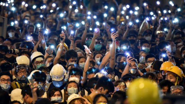 Protesters hold up their mobile phones as they gather outside the police headquarters in Hong Kong on 21 June