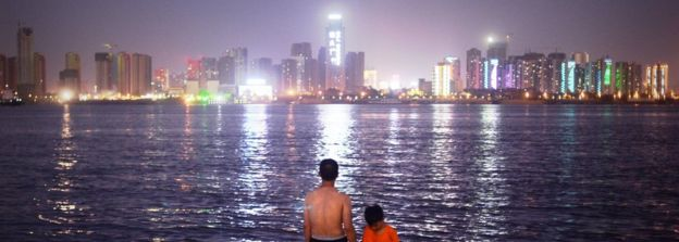 A man and child stand looking at the Wuhan skyline on the Yangtze River