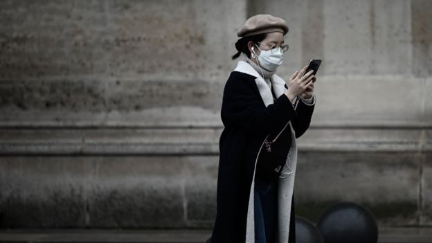 Woman in a mask check her phone, Paris, 31 January 2020
