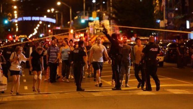Foto tirada em 22 de julho de 2018 mostra policiais e pedestres cruzando área isolada pela polícia após o ataque a tiros em Toronto