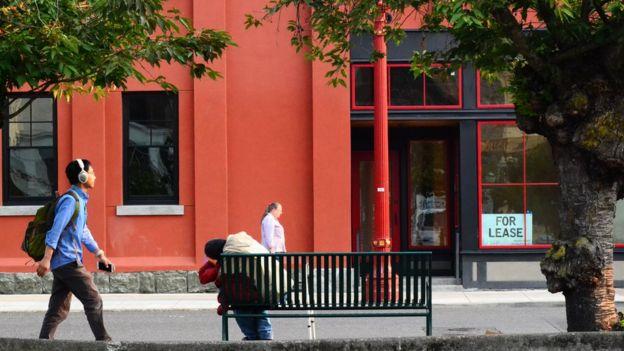 Imagem mostra dois homens caminhando na rua, enquanto outro, sem teto, está inclinado sobre um banco de praça em Portland (EUA)