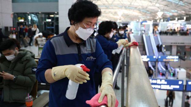 Mujer desinfectando pasamanos en un aeropuerto surcoreano.