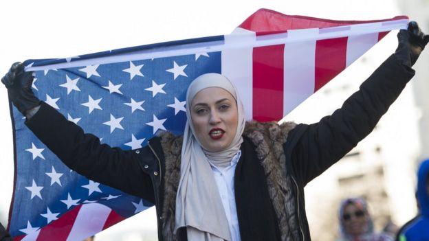 Una mujer con un velo y la bandera estadounidense protesta contra Donald Trump en Washington DC el 4 de febrero.