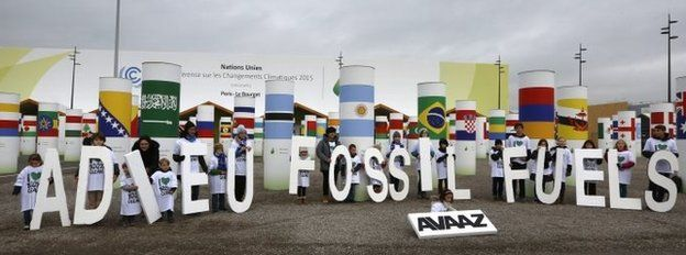 """Children display giant letters reading """"Adieu (Bye) Fossil Fuels"""", during the COP21 World Climate Change Conference"""