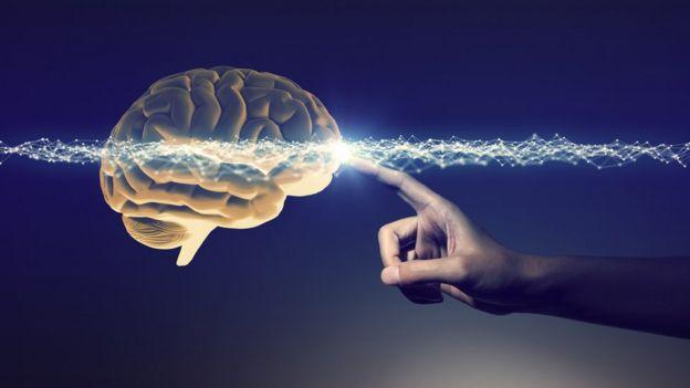 Imagen de un cerebro artificial tocado por una mano y un halo de luz brillante.
