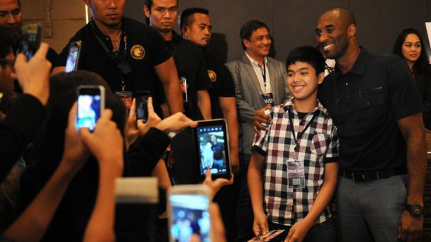 Kobe Bryant poses with a fan in Manila, Philippines in 2013