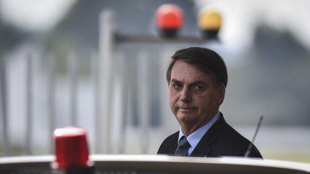 Bolsonaro em área externa, perto de carro, de onde se pode ver sinalizadores de viaturas