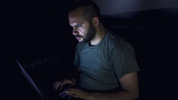 رجل يجلس أمام كمبيوتر ليلا