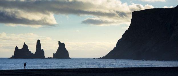Turis di pantai Reynisfjara dekat desa Vík i Myrdal, Islandia Selatan