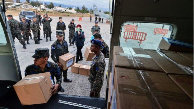 Militares carregam caixas de papelão.