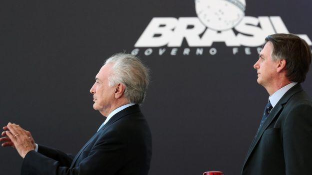 Michel Temer e Jair Bolsonaro olham para a mesma direção, com feição suave, durante evento em Brasília; Temer bate palmas