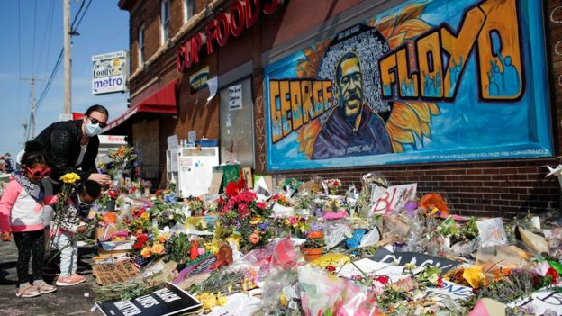 A woman and children put flowers at a makeshift memorial honoring George Floyd, at the spot where he was taken into custody, in Minneapolis, Minnesota, U.S.