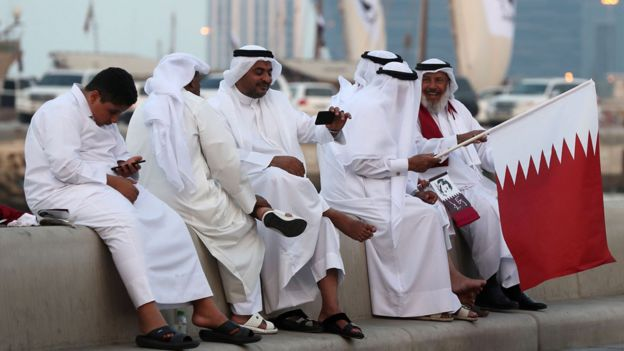Qataris wave their national flag