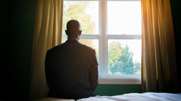 Homem sentado na cama em frente a janela