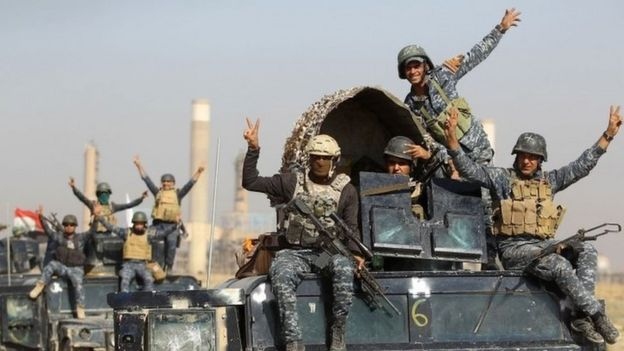 Iraqi forces flash a victory sign while driving past an oil production plant near Kirkuk. Photo: 16 October 2017