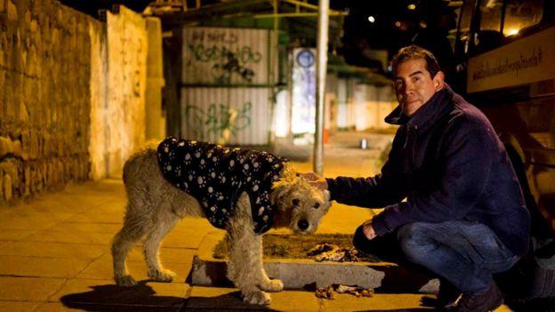 Ferchy junto a uno de los perros que alimenta.