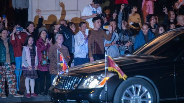 Hanoi residents and members of the media look on as a car believed to be carrying North Korean leader Kim Jong-un passes by after the first meeting between Mr Kim and President Donald Trump at the Hanoi summit on February 27, 2019