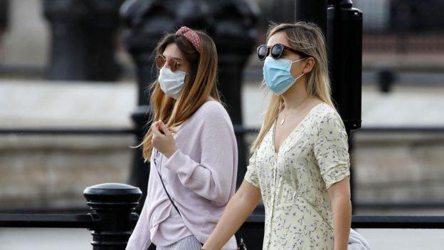 Two women walking wearing face masks