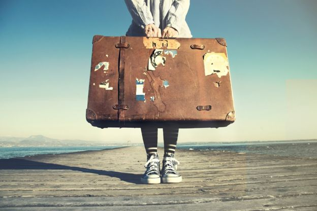 Stock image of young woman with a suitcase