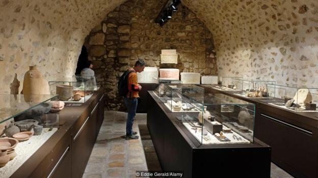 Imagem mostra visitante observando acervo do Museu Terra Santa de Jerusalém