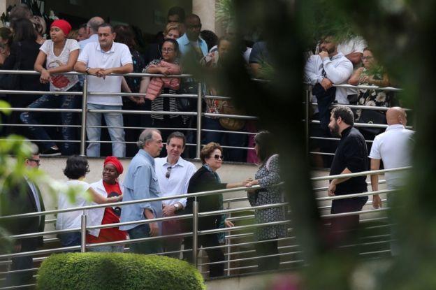 Ex-presidente Dilma Rousseff sobe rampa de cemitério para participar do velório do neto do ex-presidente Lula. Imagem também mostra outras pessoas nas proximidades