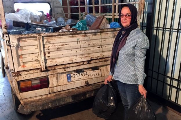 Khadija Farhat holding rubbish bags, standing next to a lorry