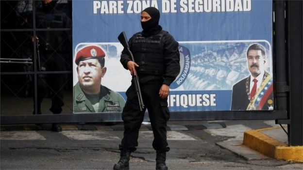 Members of the Bolivarian National Intelligence Service (SEBIN) stand guard next to a banner with the images of Venezuela's President Nicolas Maduro and Venezuela's late President Hugo Chavez, outside a detention centre, where a riot occurred, according to relatives, in Caracas, Venezuela May 16, 2018.