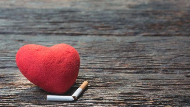 Um objeto em formato de coração ao lado de cigarro partido