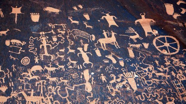 Una rueda entre los petroglifos -diseños simbólicos grabados en rocas- de Newspaper Rock State Historic Monument