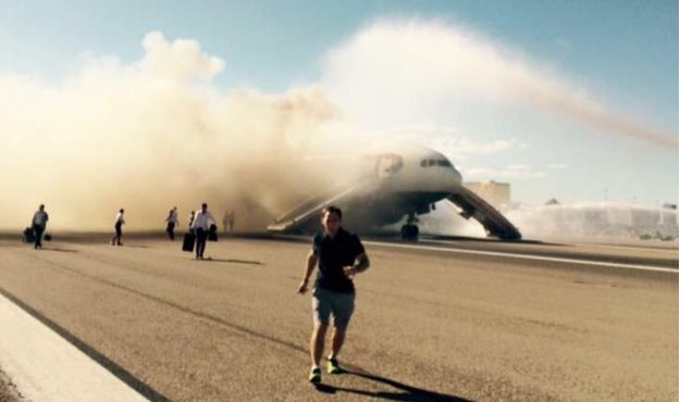 A passenger runs as the smoke billows from the plane 9 September 2015