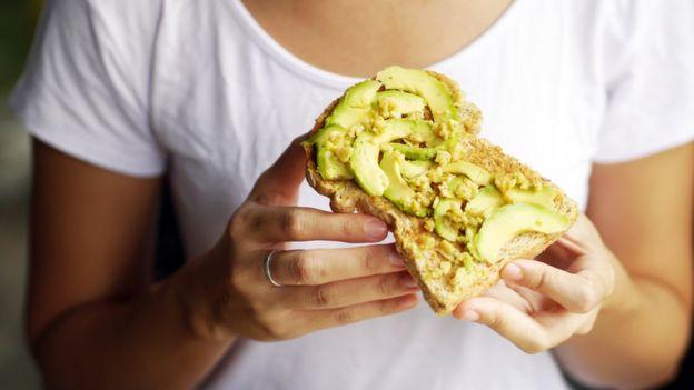 Mulher segura torrada com abacate