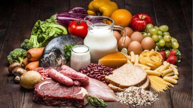 Mesa com diversos alimentos, como leite, peixe, ovos e frutas