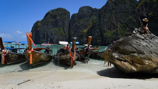 Boats and a tourist on Maya Bay before it was closed