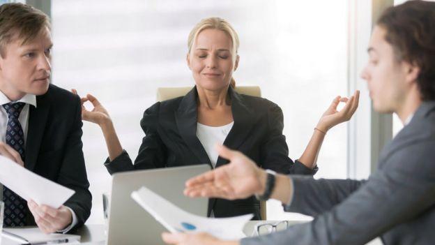 Una mujer hace relajación frente a dos hombres que discuten.
