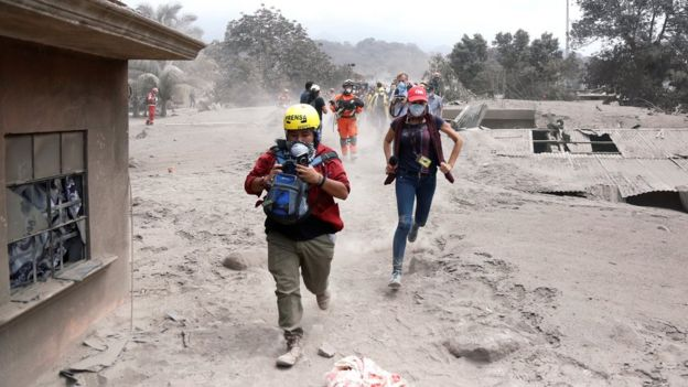 Media members reacts at an area affected by the eruption of the Fuego volcano in the community of San Miguel Los Lotes in Escuintla, Guatemala June 5, 2018.