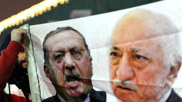 Un manifestante contra el gobierno muestra una pancarta con las imágenes de Erdogan y Gülen.